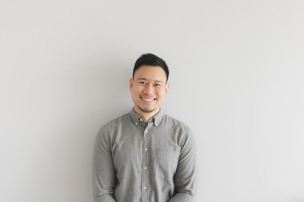 Uśmiech szczęśliwej twarzy zwykłego człowieka w szarej koszuli. koncepcja czarującego i pozytywnego myślenia.