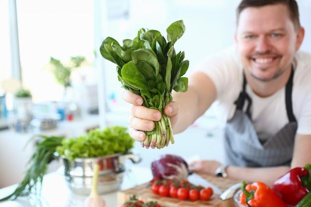 Uśmiech szefa kuchni pokazuje zielony aromatyczny ziołowy pakiet