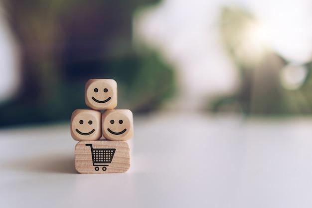 Uśmiech twarz i ikona koszyka na drewnianej kostce. optymistyczna osoba lub ludzie czujący się w środku i ocena usług podczas zakupów, koncepcja satysfakcji w biznesie.