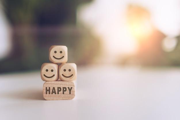 Uśmiech twarz i szczęśliwy słowo na drewnianym sześcianie. optymistyczna osoba lub ludzie czujący się w środku.