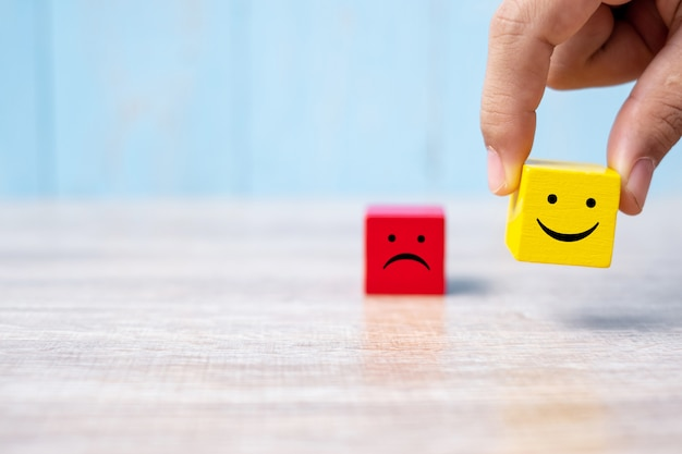 Uśmiech twarz na żółtym drewnianym sześcianie. ocena usługi, ranking, ocena klienta