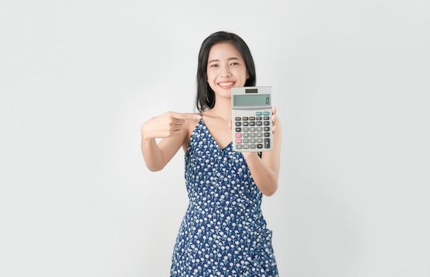Uśmiecha się azjatyckiej kobiety wskazuje palcowego kalkulatora odizolowywającego na szarym tle