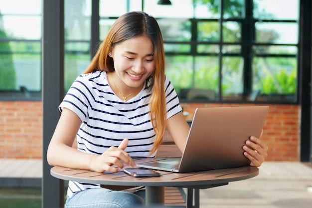 Uśmiecha się azjatykciej dziewczyny używa wiszącą ozdobę i laptop przy kawiarnią