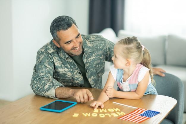 Uśmiecha się do córki. przystojny brodaty oficer wojskowy uśmiechający się do swojej uroczej, promieniującej córki