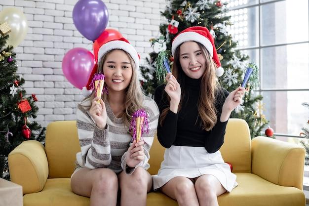 Uśmiecha się dwóch młodych azjatyckich kobiet razem z tańcem w domu w świętować boże narodzenie