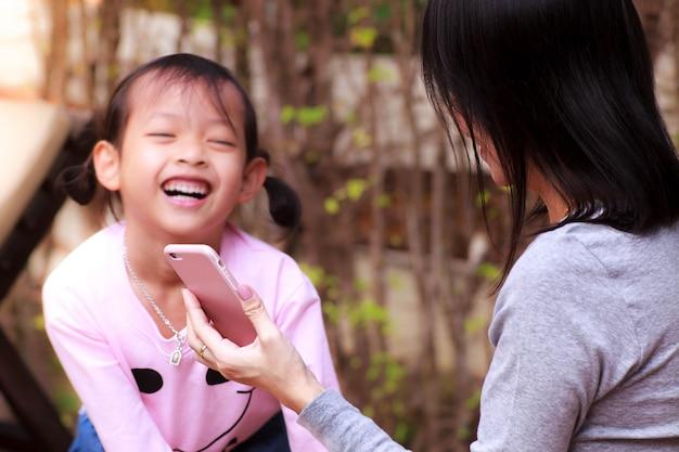 Uśmiecha się dziecko dziewczyny w szczęśliwym z bawić się smartphone.