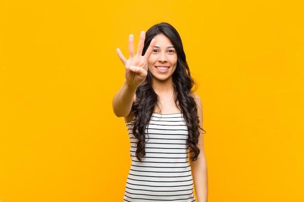 Uśmiecha Się I Wygląda Przyjaźnie, Pokazuje Numer Cztery Lub Czwarty Ręką Do Przodu, Odliczając Premium Zdjęcia