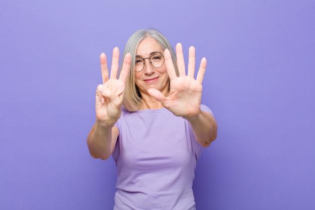 Uśmiecha się i wygląda przyjaźnie, pokazuje numer osiem lub ósmy ręką do przodu, odliczając