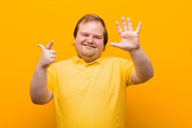 Uśmiecha się i wygląda przyjaźnie, pokazuje numer siedem lub siódmy z ręką do przodu, odliczając