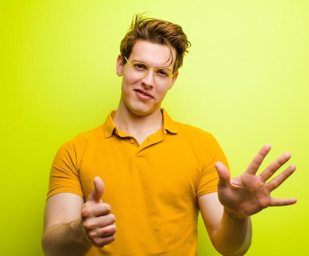 Uśmiecha się i wygląda przyjaźnie, pokazuje numer sześć lub szósty ręką do przodu, odliczając