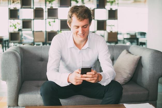 Uśmiecha się przystojny biznesmen przy użyciu smartphone