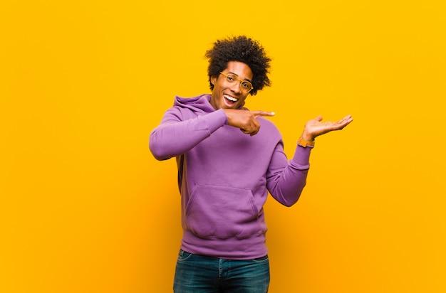 Uśmiecha się wesoło i wskazuje na kopię miejsca na dłoni z boku, pokazując lub reklamując przedmiot