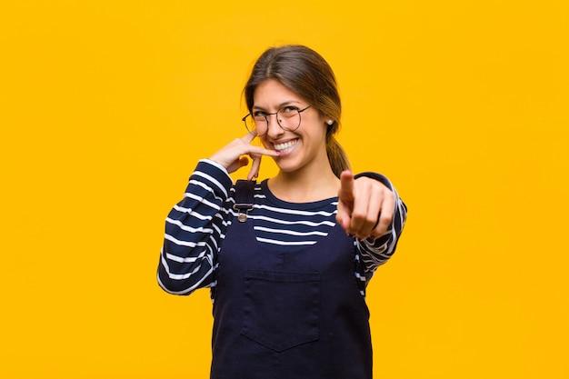Uśmiecha się wesoło i wskazuje podczas wykonywania połączenia, a następnie gestem, rozmawia przez telefon