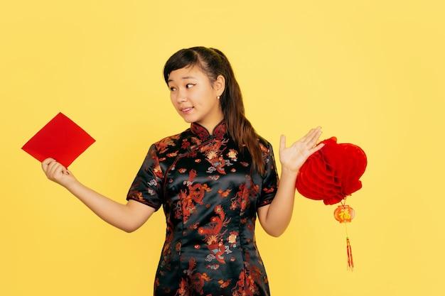 Uśmiecha się z lampionem i kopertą. szczęśliwego chińskiego nowego roku 2020. portret azjatyckiej młodej dziewczyny na żółtym tle. modelka w tradycyjne stroje wygląda na szczęśliwą. świętowanie, emocje. copyspace.