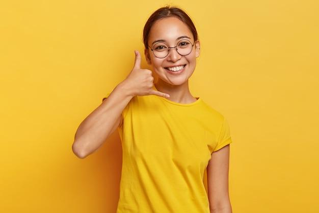 """Uśmiecha się zachwycona azjatka pokazuje gest """"zadzwoń do mnie"""", robi gest ręką telefonu, ma szczęśliwy wyraz twarzy, zdrową skórę, nosi okulary i stroje codzienne, odizolowane na żółtej ścianie. język ciała."""