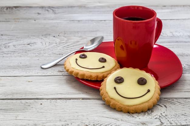 Uśmiechać się ciastka na czerwonym talerzu z filiżanką kawy, drewniane tło, jedzenie