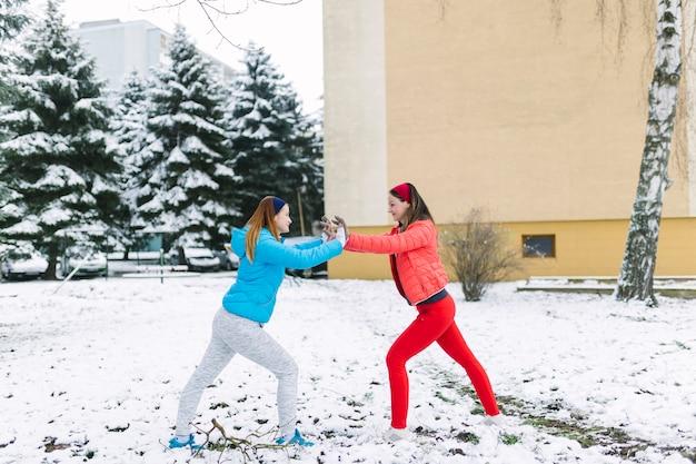 Uśmiechać się dwa żeńskiego przyjaciela walczy przy outdoors w zimie