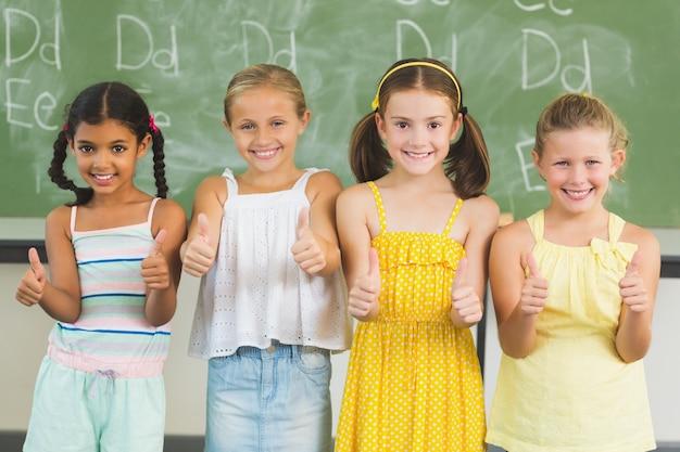 Uśmiechać się dzieciaków pokazuje aprobaty w sala lekcyjnej