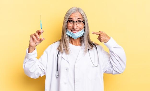 Uśmiechać się pewnie wskazując na swój szeroki uśmiech, pozytywne, zrelaksowane, usatysfakcjonowane nastawienie. koncepcja lekarza i szczepionki