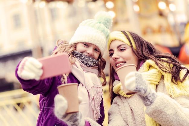 Uśmiechaj się. urocza brunetka kobieta patrząc na telefon i siedzi w pobliżu córki
