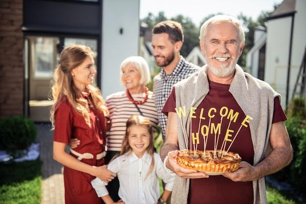 Uśmiechaj się. zadowolony emeryt trzymający tort w obu rękach czekając na gości