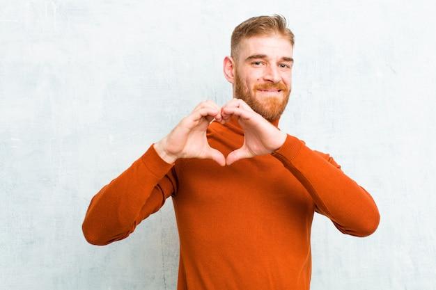 Uśmiechając się i czując się szczęśliwym, uroczym, romantycznym i zakochanym, tworząc kształt serca obiema rękami