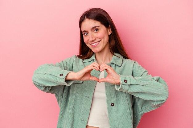 Uśmiechając się i pokazując kształt serca rękami.
