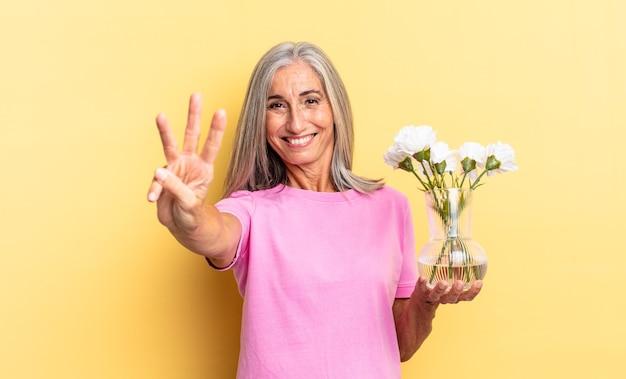 Uśmiechając się i wyglądając przyjaźnie, pokazując cyfrę trzy lub trzecią ręką do przodu, odliczając trzymając ozdobne kwiaty
