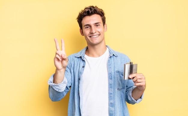 Uśmiechając się i wyglądając przyjaźnie, pokazując numer dwa lub sekundę z ręką do przodu, odliczając. koncepcja kolby z alkoholem