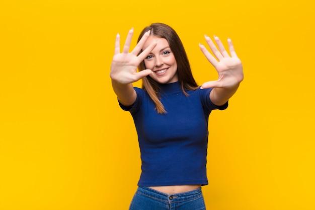 Uśmiechając się i wyglądając przyjaźnie, pokazując numer dziesięć lub dziesiąty ręką do przodu, odliczając