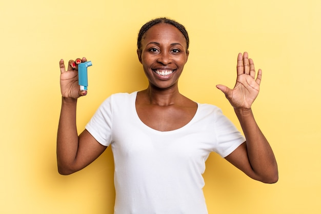 Uśmiechając się i wyglądając przyjaźnie, pokazując numer pięć lub piąty z ręką do przodu, odliczając. koncepcja astmy