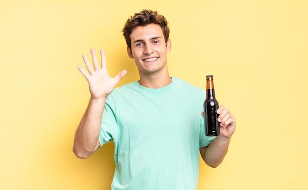 Uśmiechając się i wyglądając przyjaźnie, pokazując numer pięć lub piąty z ręką do przodu, odliczając. koncepcja butelki piwa