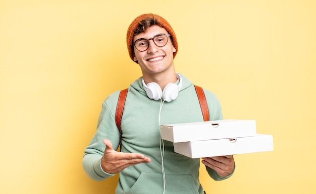 Uśmiechając się radośnie, czując się szczęśliwy i pokazując koncepcję w przestrzeni kopii dłonią. koncepcja pizzy