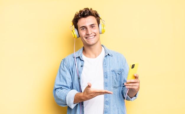 Uśmiechając się radośnie, czując się szczęśliwy i pokazując koncepcję w przestrzeni kopii dłonią. koncepcja słuchawek i smartfona