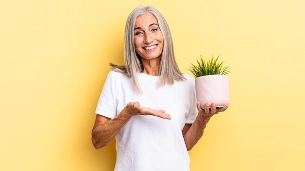 Uśmiechając się radośnie, czując się szczęśliwy i pokazując koncepcję w przestrzeni kopii z dłonią trzymającą roślinę ozdobną