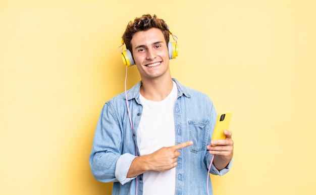 Uśmiechając się radośnie, czując się szczęśliwy i wskazując na bok i do góry, pokazując obiekt w przestrzeni kopii. koncepcja słuchawek i smartfona