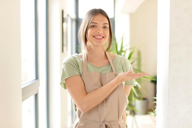 Uśmiechając się radośnie, czując się szczęśliwym i pokazując koncepcję w przestrzeni kopii dłonią
