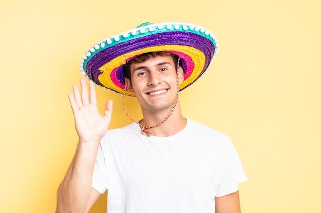 Uśmiechając się radośnie i radośnie, machając ręką, witając cię i pozdrawiając lub żegnając. koncepcja meksykańskiego kapelusza
