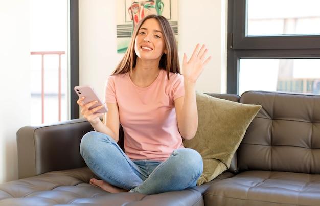 Uśmiechając się radośnie i radośnie, machając ręką, witając cię i pozdrawiając lub żegnając się