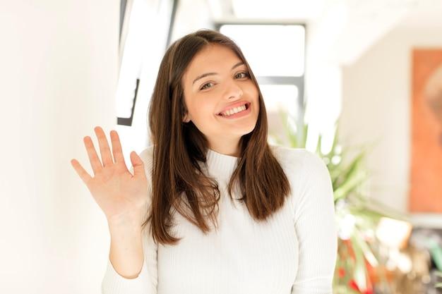Uśmiechając się radośnie i wesoło machając ręką i witając cię lub żegnając się