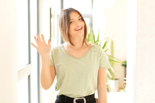 Uśmiechając się radośnie i wesoło, machając ręką i witając się lub żegnając się