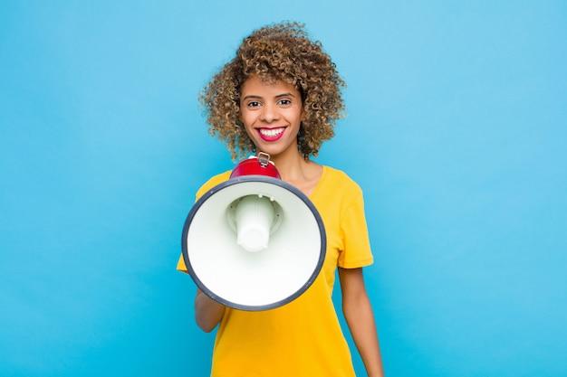 Uśmiechając się radośnie z ręką na biodrze i pewną siebie, pozytywną, dumną i przyjazną postawą