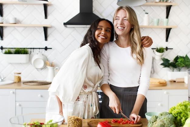 Uśmiechająca się blond kaukaska kobieta kroi pieprz, a brunetka mulat przytula ją w białej nowoczesnej kuchni