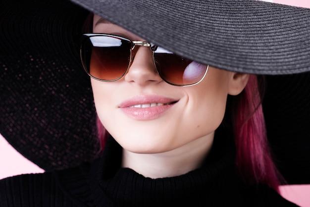 Uśmiechająca się dziewczyna w okularach i kapeluszu