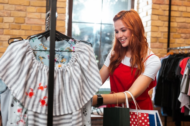 Uśmiechająca się dziewczyna. wesoła, emocjonalna młoda dziewczyna uśmiecha się i czuje się szczęśliwa, odwiedzając modny sklep z odzieżą i patrząc na nową kolekcję