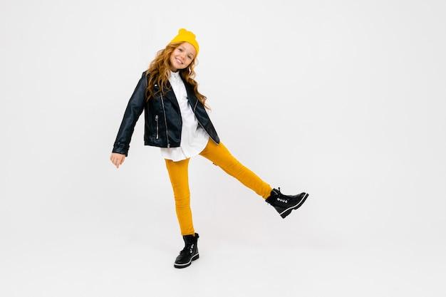 Uśmiechająca się stylowa, urocza uczennica w białej koszuli, rozpiętej czarnej skórzanej kurtce, żółtych spodniach, z żółtym kapeluszem na głowie, pozowanie na białym z miejsca na kopię