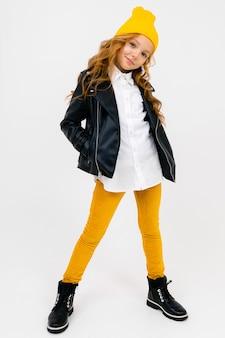 Uśmiechająca się stylowa, urocza uczennica w białej koszuli, skórzanej czarnej kurtce z żółtą czapką na głowie pozuje na białym