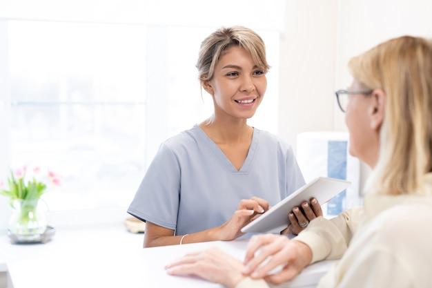 Uśmiechający się administrator salonu piękności rasy mieszanej w peelingach za pomocą tabletu, aby sprawdzić wizytę klientów