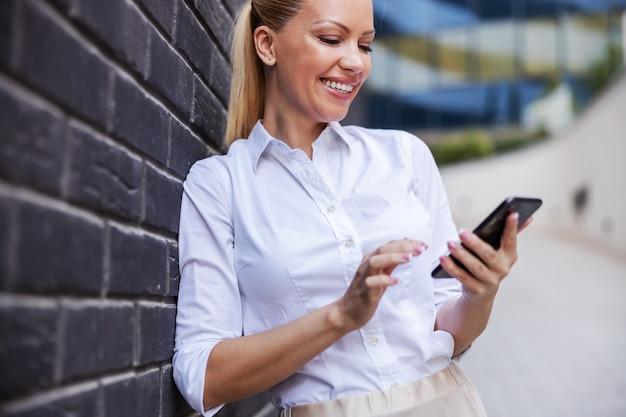Uśmiechający się atrakcyjny pozytywny blond modna bizneswoman opierając się na ścianie podczas wysyłania wiadomości tekstowej przez telefon.