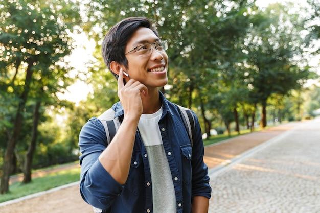 Uśmiechający się azjatycki student płci męskiej w okularach i słuchawkach słuchanie muzyki, patrząc od hotelu